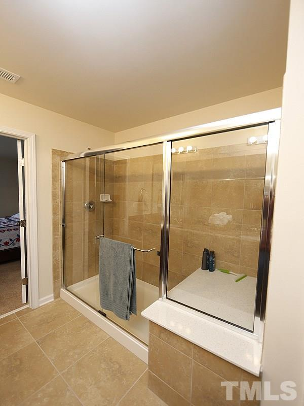 Enjoy your shower time in this large, tiled, walk-in shower with a seat.