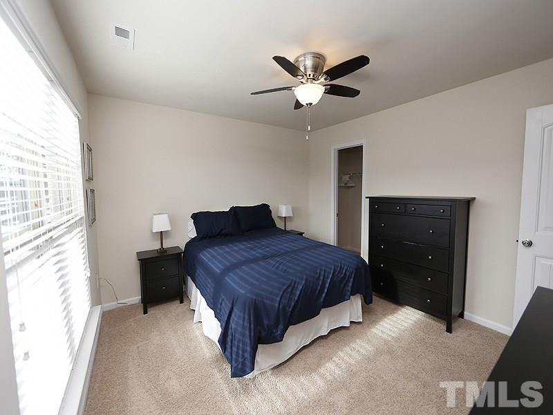 This secondary bedroom has a large walk-in closet and there is a fan.