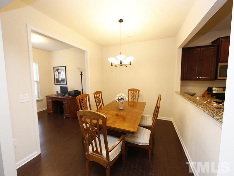 A view of the dining room with sunroom to the left and kitchen to the right.