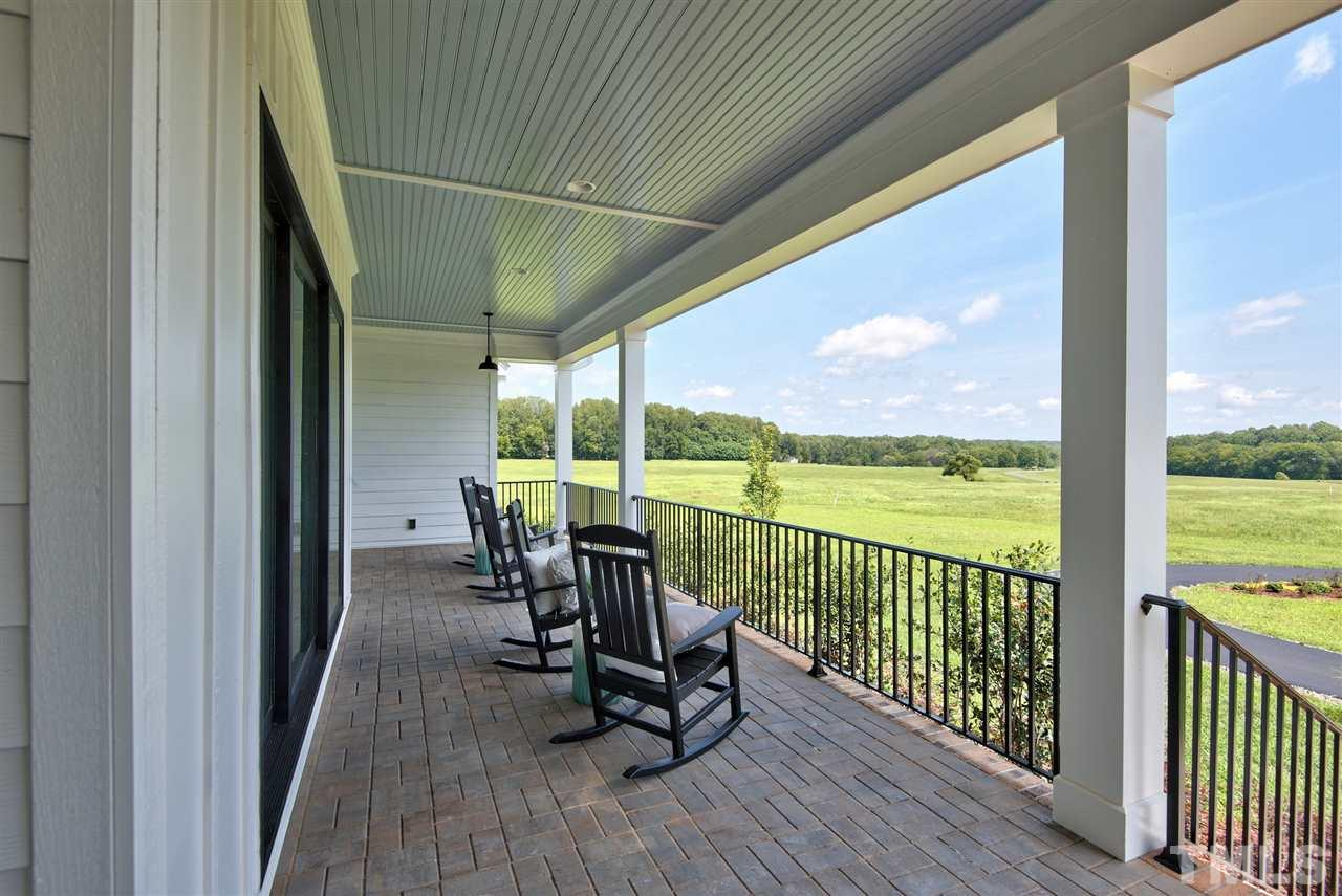 Classic rocking chair porch with view of common pond.