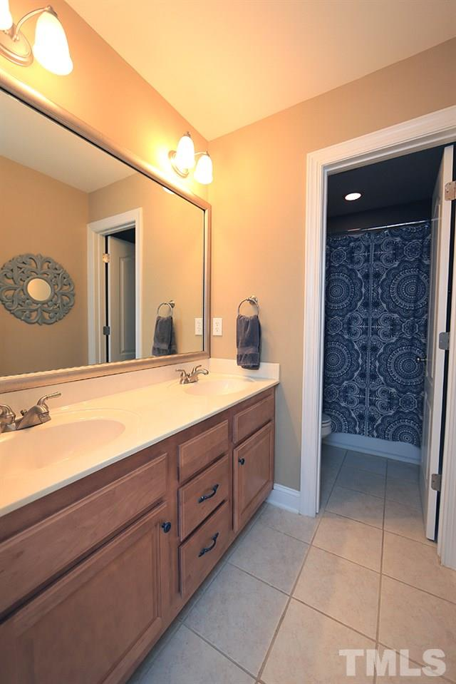 Dual sinks. Door to toilet and tub/shower.