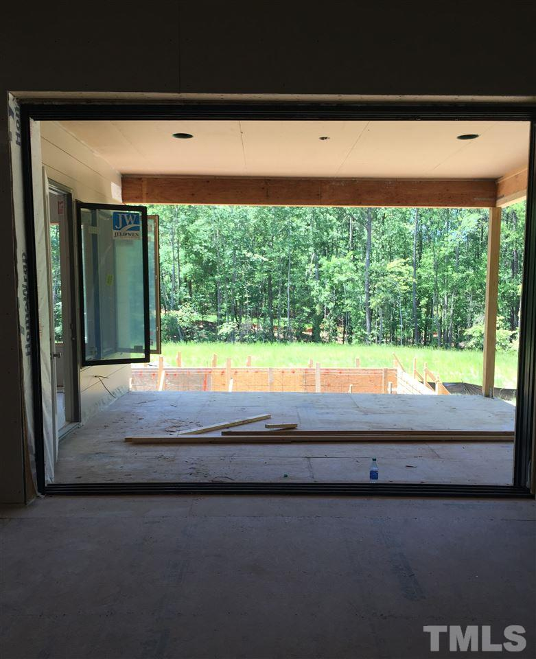 Family Room with folding glass doors looking out to Screened Porch then to the pool.