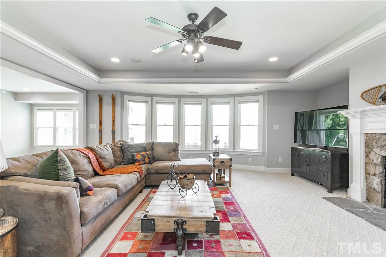 Bonus family room in the basement with rope lighting, stone fireplace and bright windows.