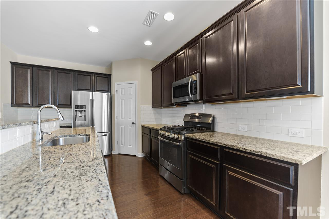 The kitchen has espresso cabinets, granite counters, subway tile backsplash, corner walk in pantry and stainless appliances.