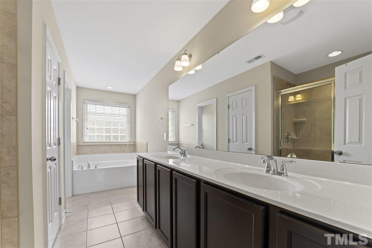 The master bathroom has an oversized long vanity with 2 sinks, garden tub, large walk in shower and separate commode room.  There is also a linen closet with an outlet inside (handy).