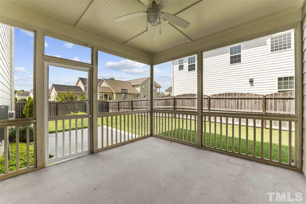 The screened porch opens onto a patio overlooking the fenced backyard.