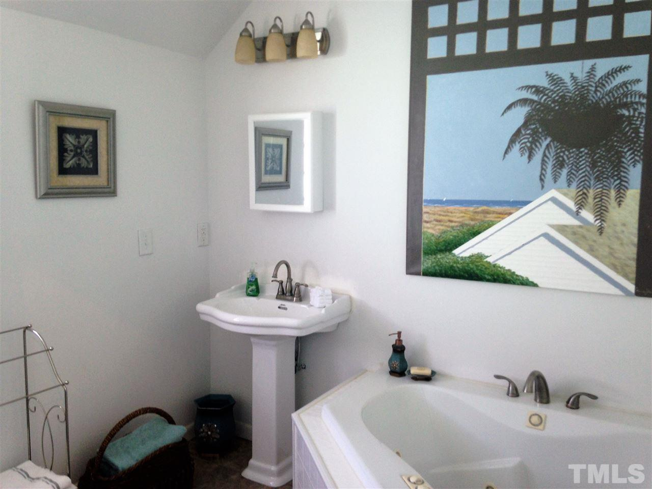 Private whirlpool tub with separate toilet area adjacent to the walk-in closet for dressing.