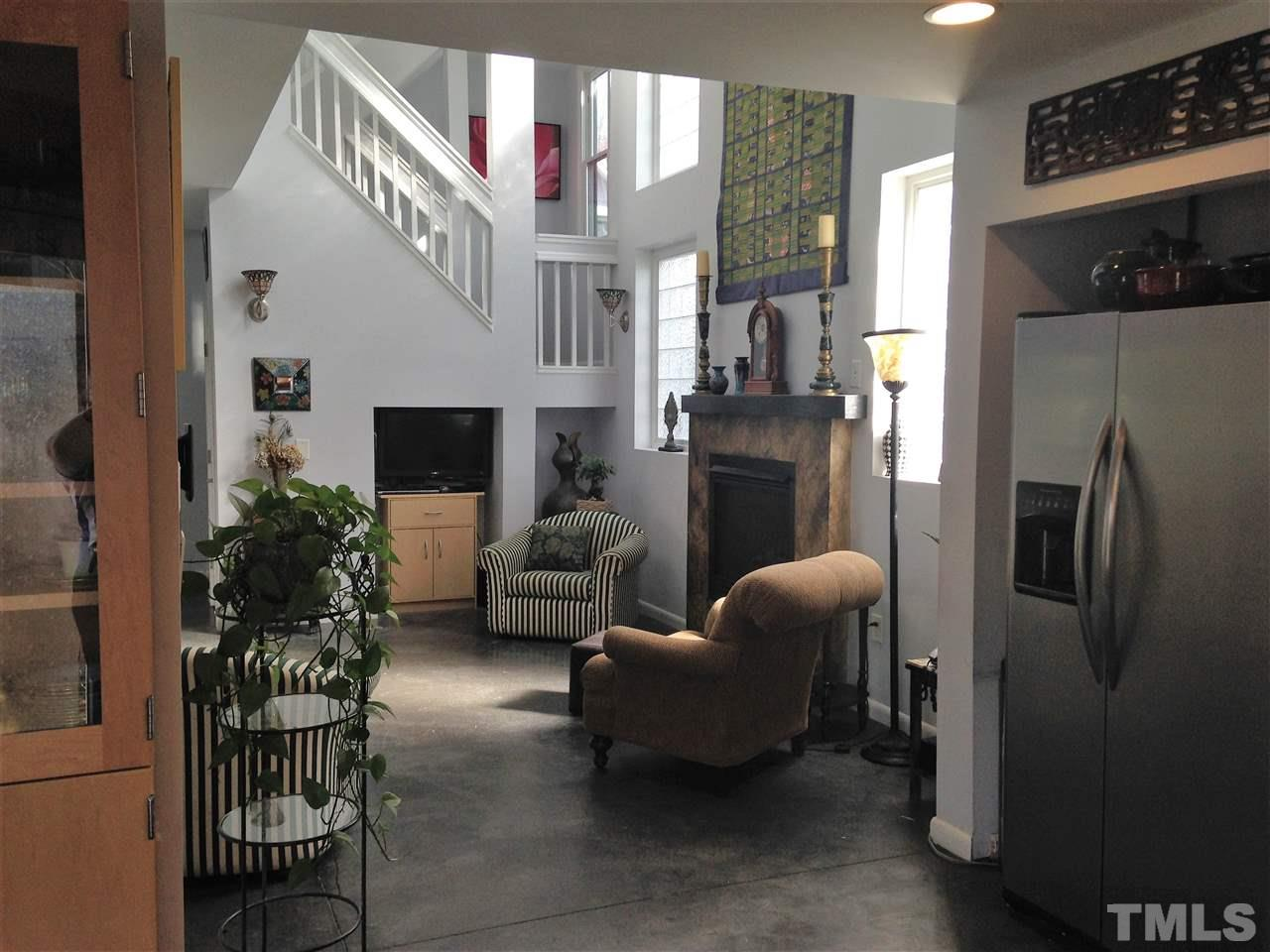 The house has a wonderful open and airy feeling with rooms flowing gracefully throughout. From the kitchen door entrance, you can look through the living room with soaring 2-story ceiling and see the dramatic staircase climbing to the 3rd floor.