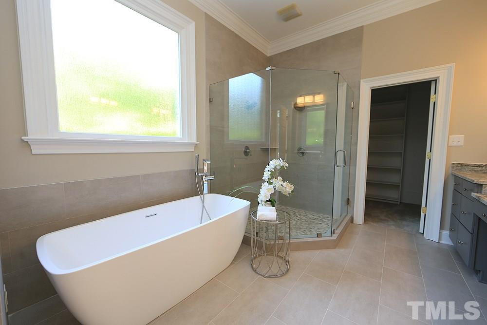 The master bath has been remodeled with a painted cabinetry, leathered marble counters, new lights and faucets, large free-standing soaking tub and huge walk-in shower with 2 shower heads.  There is a separate commode room with window.