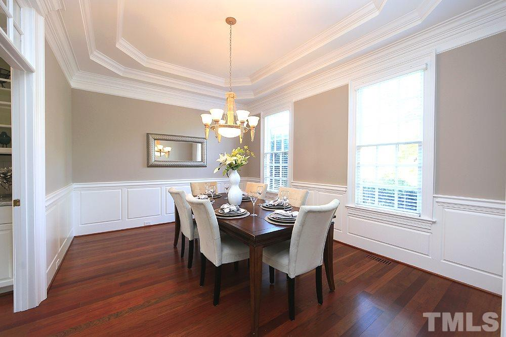 The dining room has a tiered tray ceiling and beautiful trim detail.  The custom trim detail is evident throughout the home.