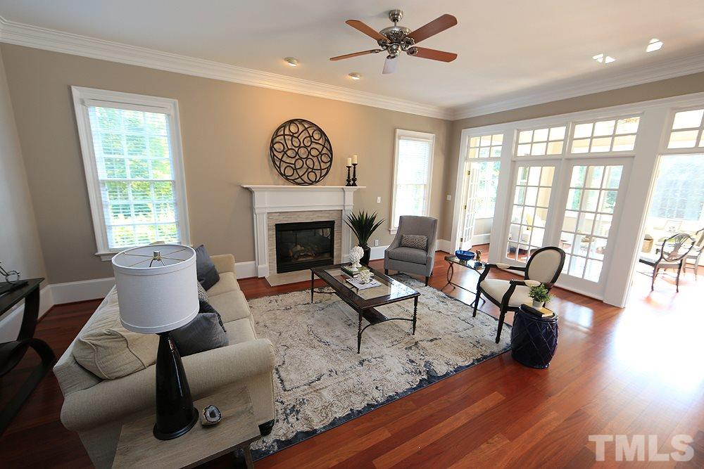 The family room opens to the kitchen/breakfast room as well as the bright sunroom.   A wall of french doors/glass separates the sunroom from the family room.