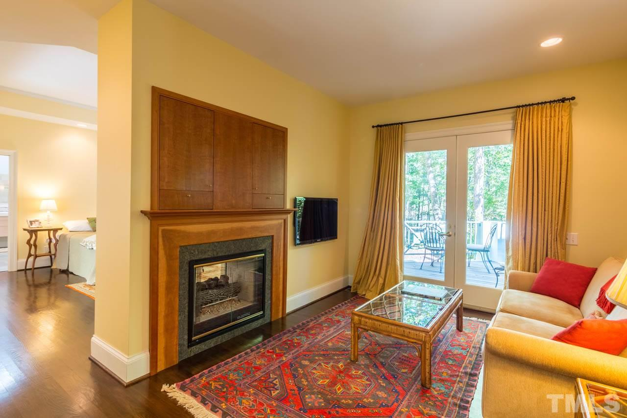 The sitting area in the master has a fireplace with custom mantle and direct deck access.