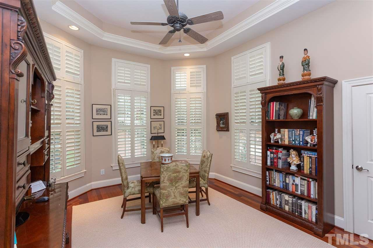 """Grand study that offers a wall of windows covered with 4"""" plantation shutters, trey ceiling, and plenty of space for desk, couch, or bookshelves."""