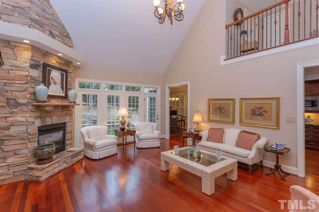 Beautiful Brazilian hardwoods gleam in this 2- story living room with stacked stone fireplace. Neutral decor allows for all kinds of discriminating tastes.
