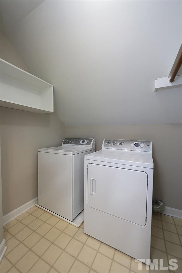 Walk in laundry room with cabinets and hanging space on second floor.
