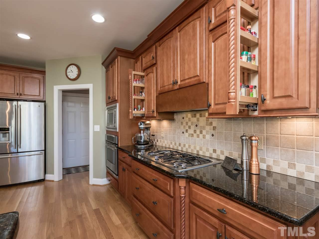 Don't miss the concealed vent over the 5-burner gas cooktop and the multiple storage areas for spices and cleaning supplies.