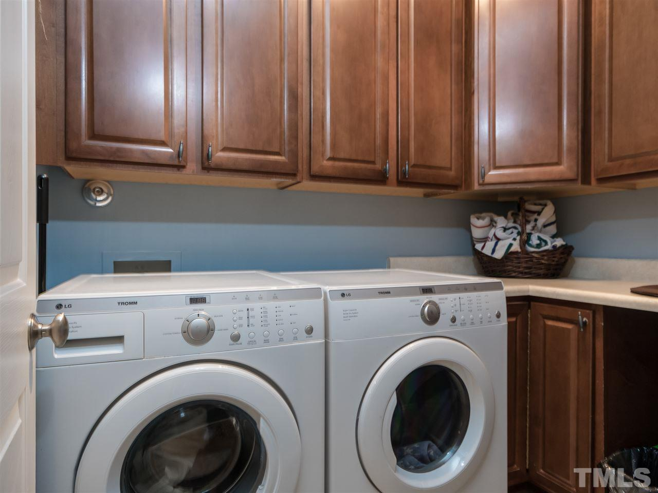 Right off the kitchen you'll find this tiled laundry room with cabinets and also a large walk-in pantry.