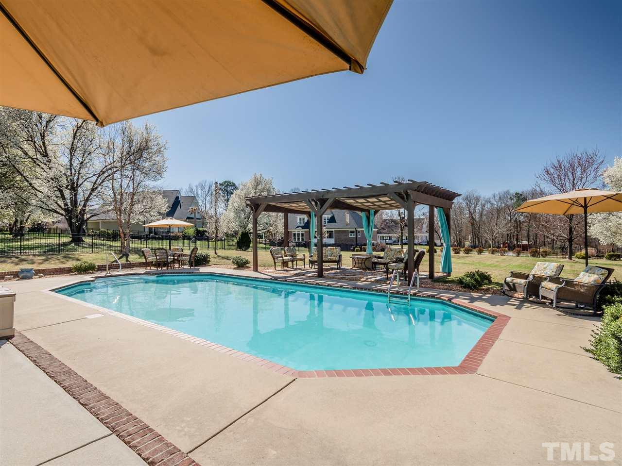 Notice the brick edging accenting the 18 x 36 in-ground pool and patio.  Wrought iron style fencing around the entire back yard!!