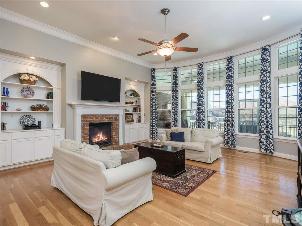 The fireplace is flanked by twin bookcases and features a raised hearth and gas logs.