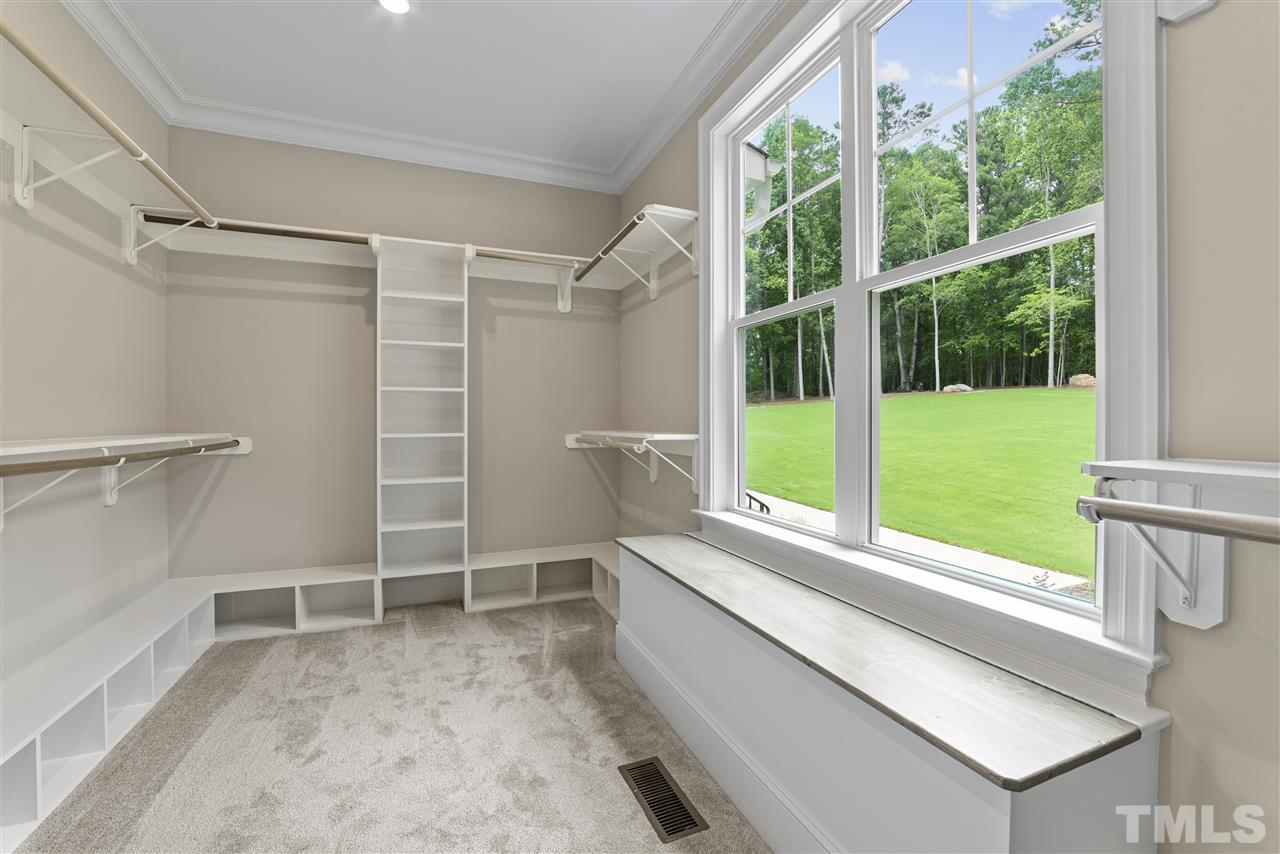 The master closet was thoughtfully planned with shoe cubbies, shelves and hanging space.  It even has window seat with storage.