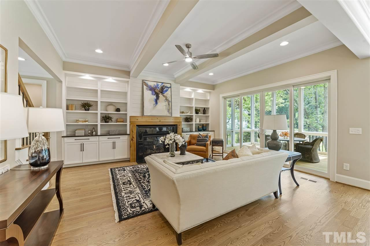 Built ins frame the wood surround gas fireplace.  Shiplap highlights the wall behind the built ins.  There is recessed lighting, beams and sliders that open to the screened porch.  Designer inspired ceiling fans and light fixtures throughout.