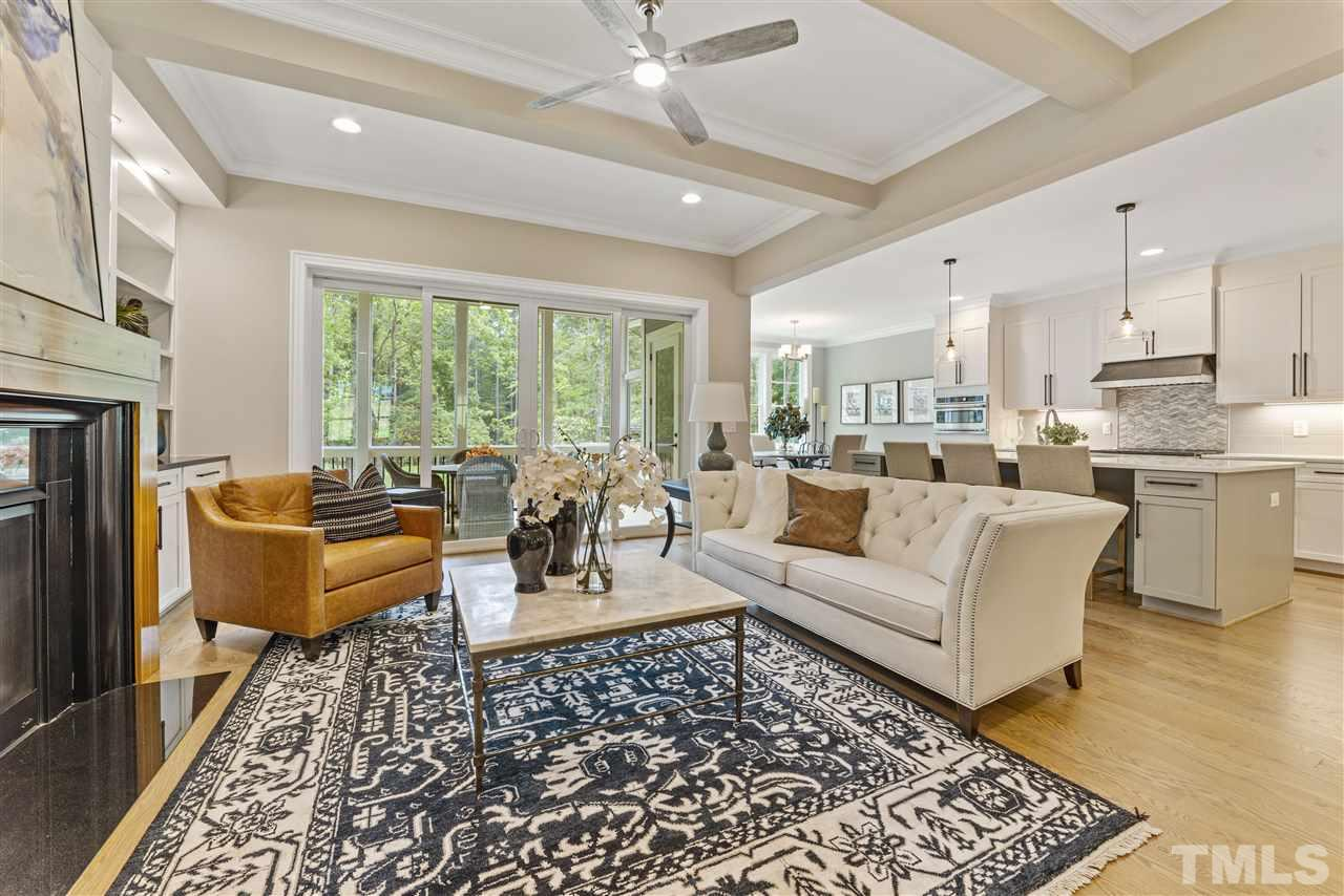 A view of the open floor plan of the family room to the kitchen and breakfast room. The natural gas fireplace has a black granite surround with stained wood mantel.