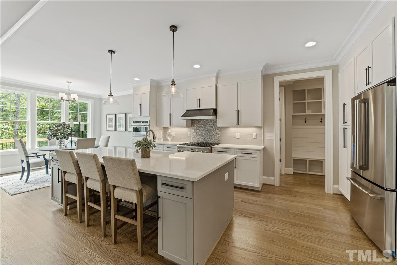 A chef's dream with GE Cafe appliances including a 6 burner gas range, dishwasher, microwave, GE Monogram fridge and a custom crafted range hood.  There is a large subway tile backsplash w/ accents behind the stove.  Undercabinet lighting for ambience.