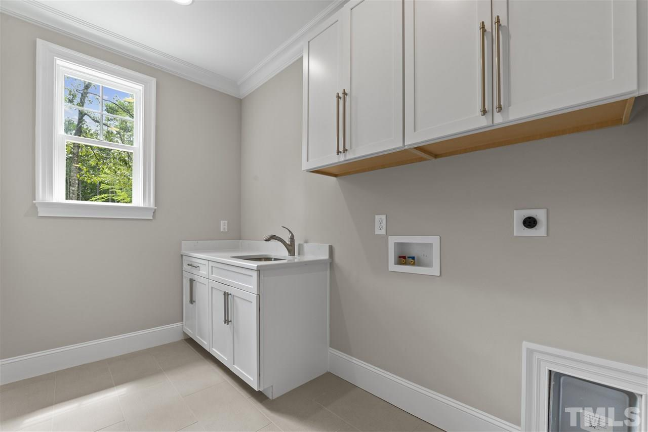The spacious and bright laundry room is in the back on the main floor by the guest suite.  It has upper and lower cabinets and a sink.