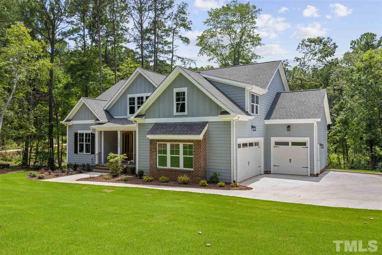 The home has a 3 car garage (double side plus single front), plus a side parking pad and a long driveway. The exterior is low maintenance fiber cement, board and batten with brick accents.
