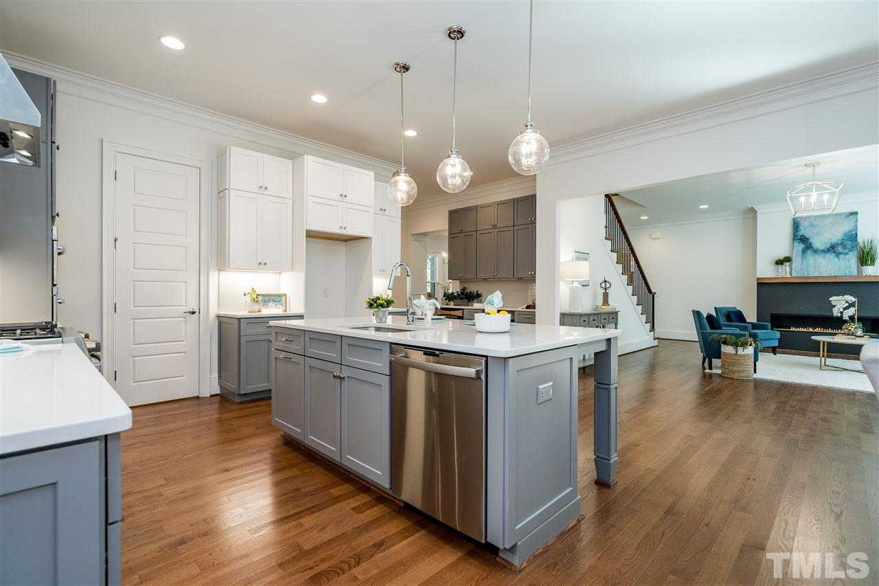 Walk-in Pantry and separate bar with wine chiller offer so much more storage in this open kitchen.
