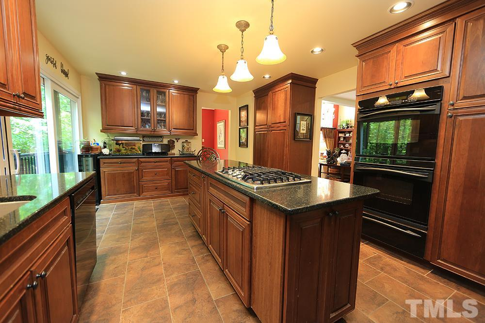 Kitchen features large island, gas cooktop, wine bar, brand new dishwasher and quartz countertops