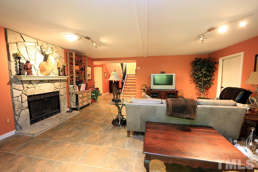 Bonus area in basement with a stone fireplace