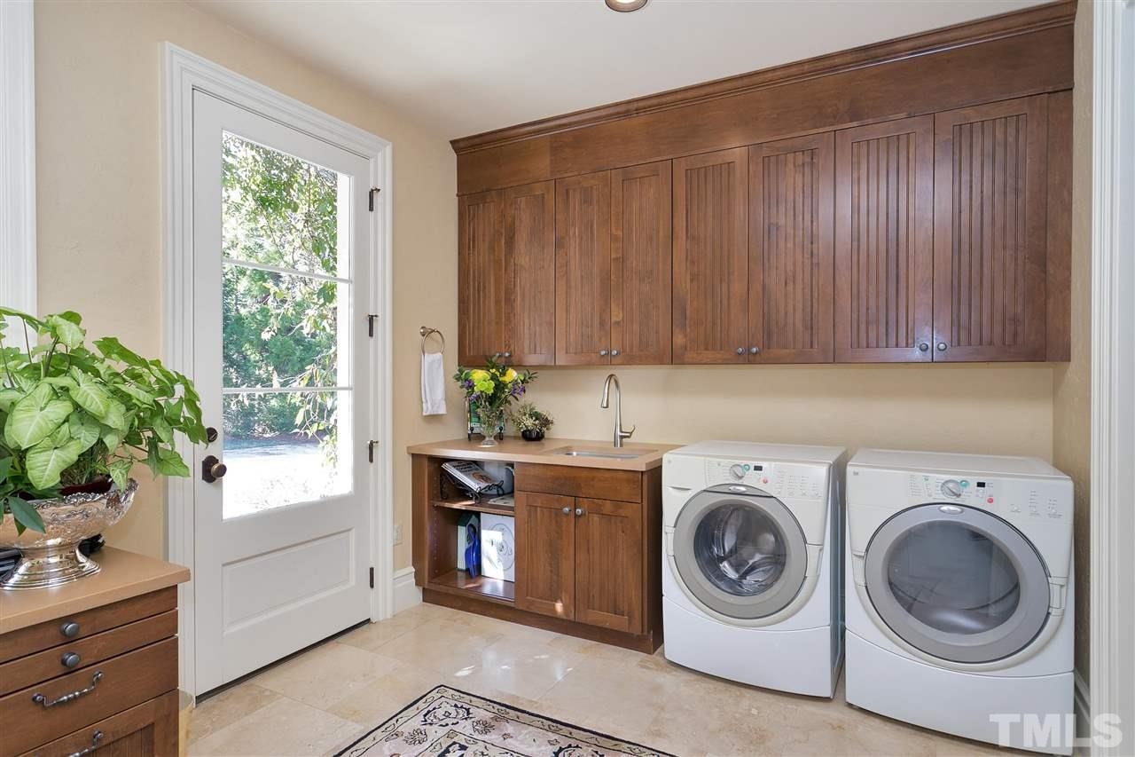 The laundry area is conveniently located on the first floor and has an exterior entrance for kids coming in from playing outside. Lots of storage, desk space and room for air drying clothing.