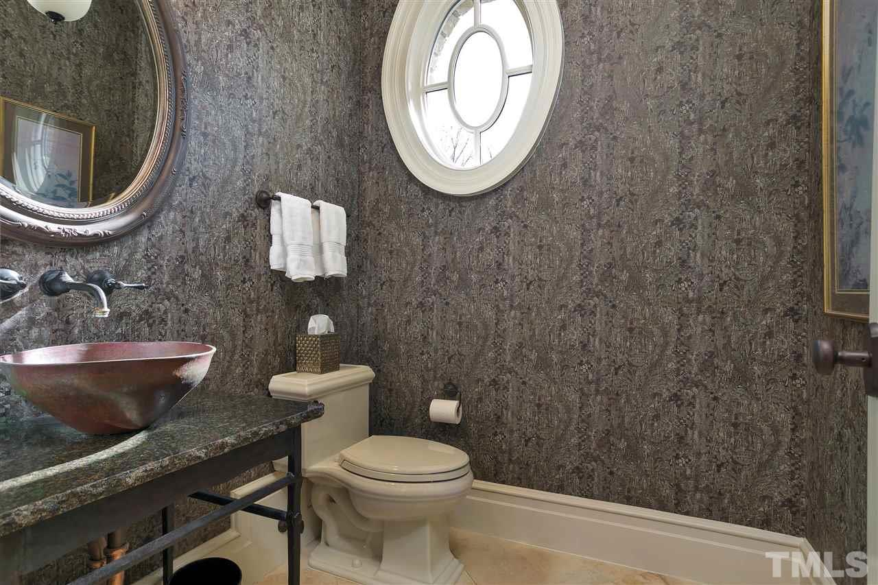 One of the lovely first floor half baths with quaint oval window, vessel sink and wall plumbing fixtures.