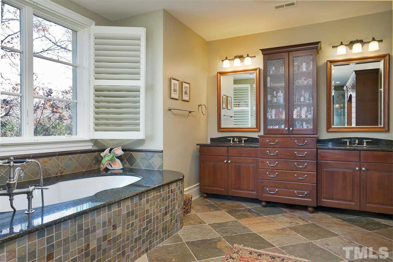 Enjoy a bubble bath in this spacious garden tub with tile surround and granite ledge. Plantation shutters, his/her sink areas, furniture-like storage finish off the exquisite details.