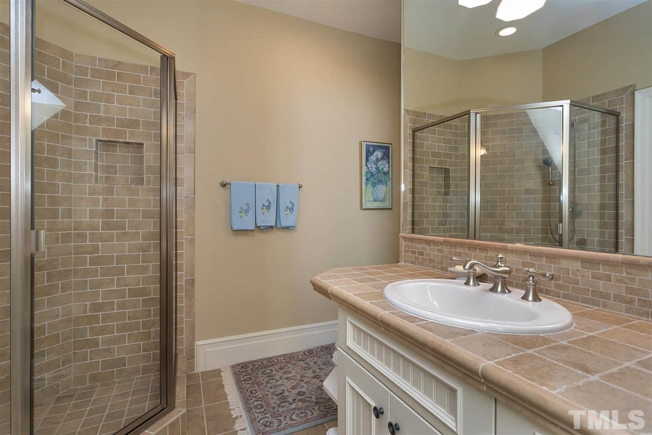 One of the stylish secondary baths. Note the tile counters, large tile shower and crisp white cabinetry. All secondary bedrooms have en-suite baths and walk-in closets.