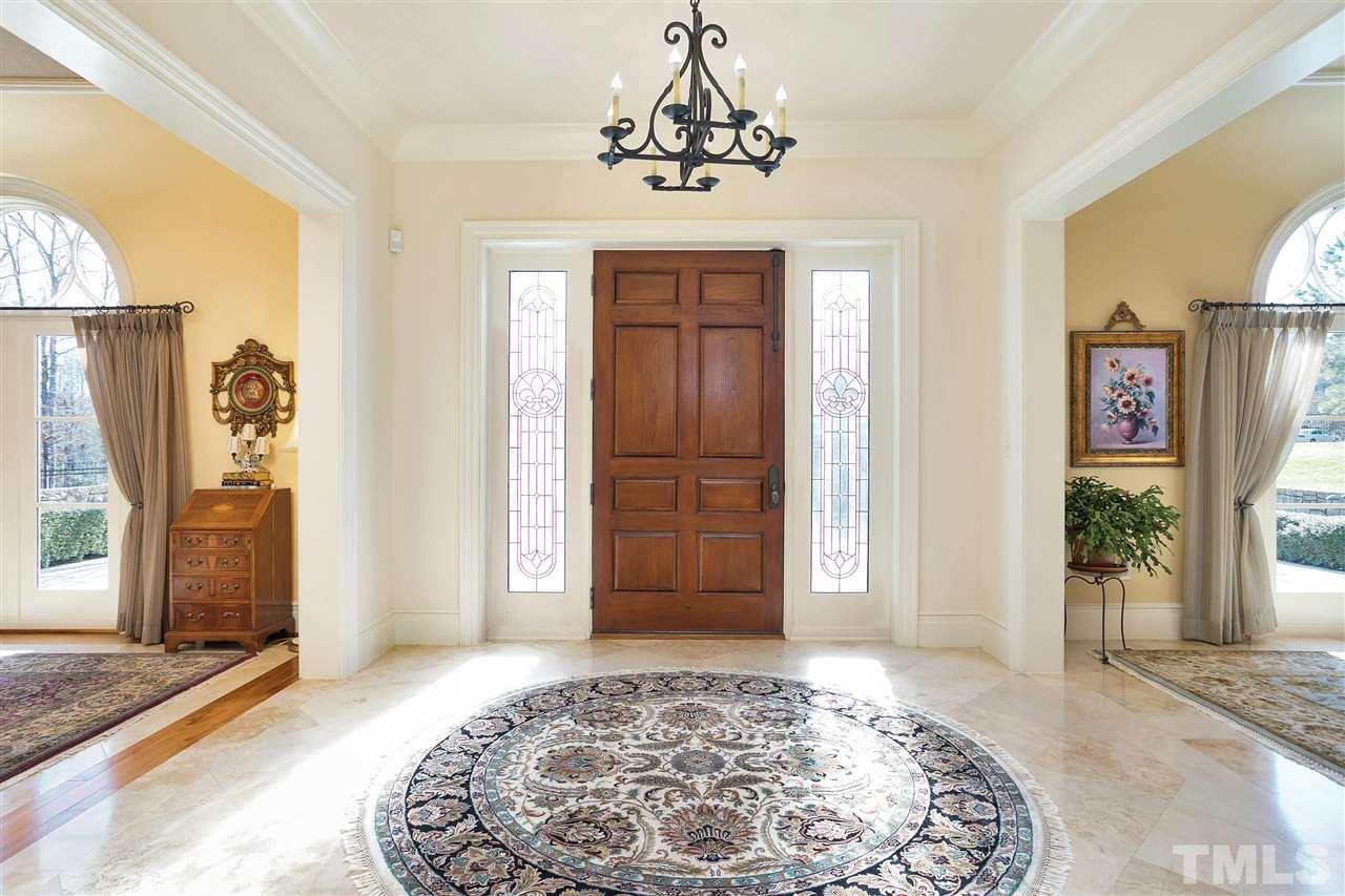 The bright, airy and open foyer greats your guests upon arrival. The leaded glass side lights and tile floors set it off from the dining room and formal living rooms on either side.
