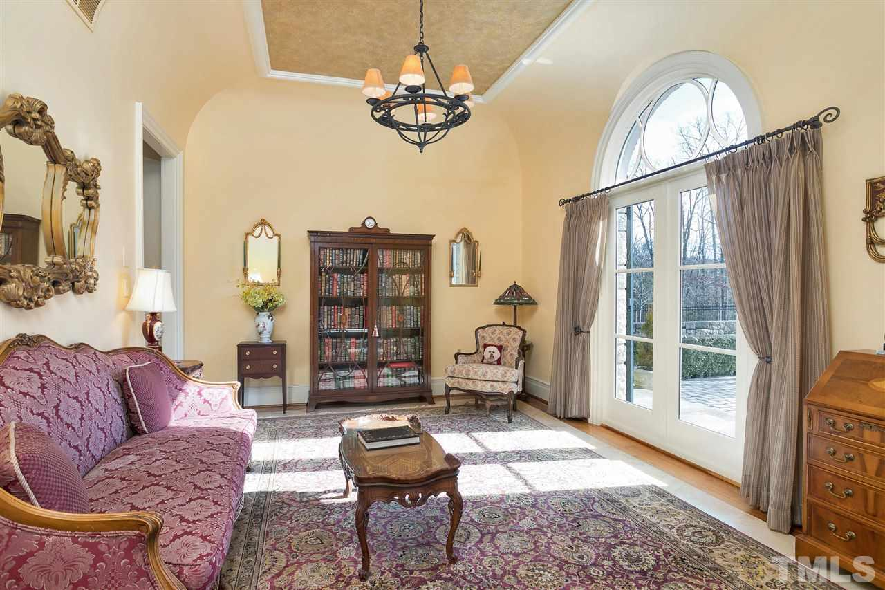 Rich wood floors adorn the formal living. Notice the arch corners of the room match those around the palladium window.