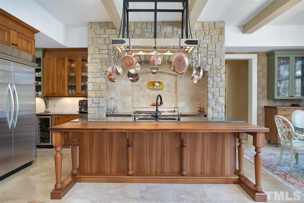 The open beam ceiling, gleaming pot rack, magnificent stone around the cooking area is much like what you'd see of European kitchens. Can't you just imagine a chef preparing a mouthwatering meal?