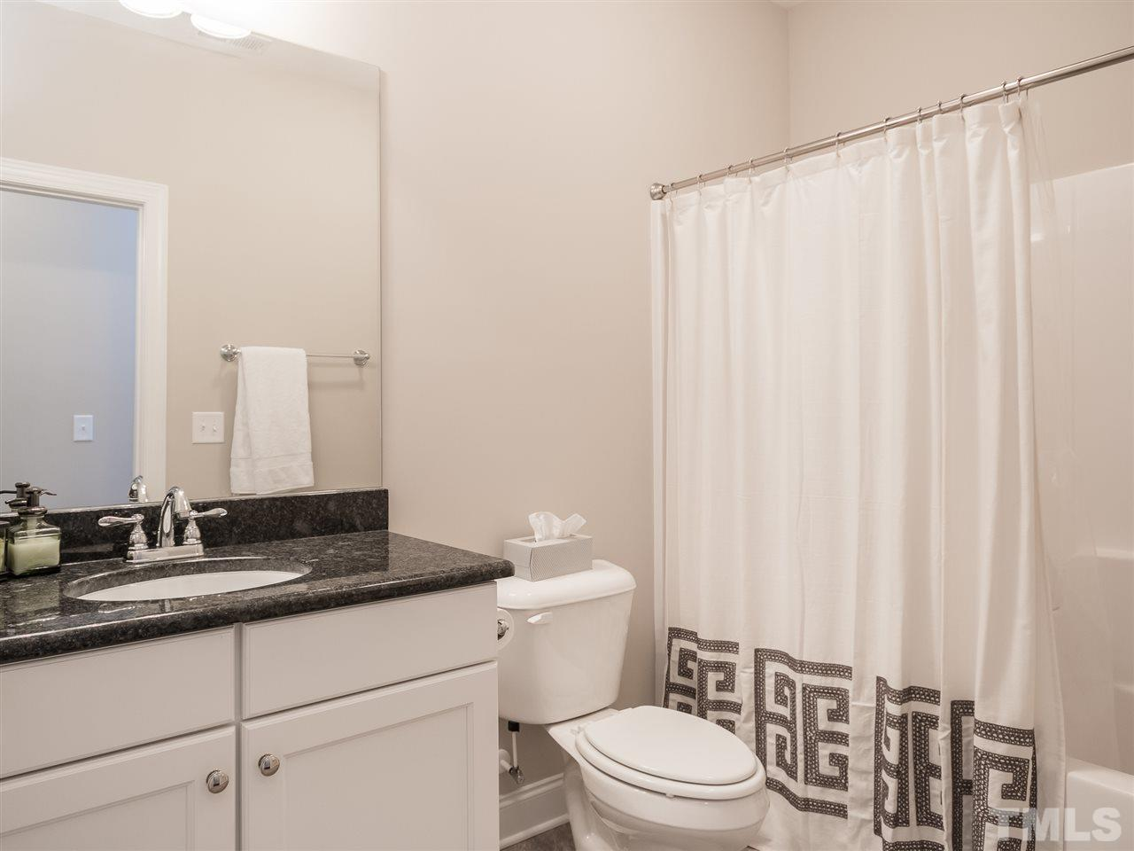 Guest bath with granite counter tops and tile floors.