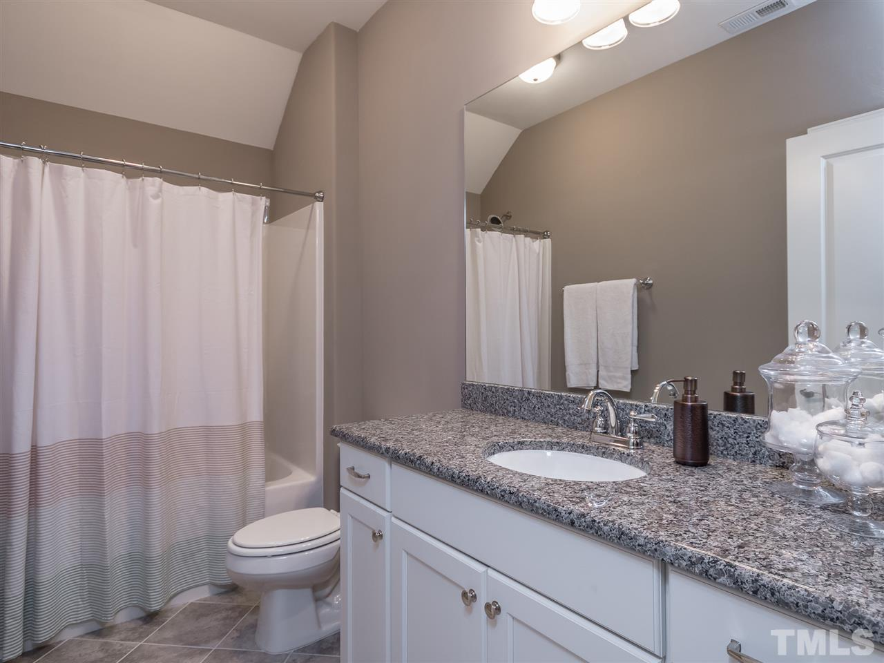 Guest bath on the second level with granite counter top and tile floor. Everything in this home looks and feels brand new.