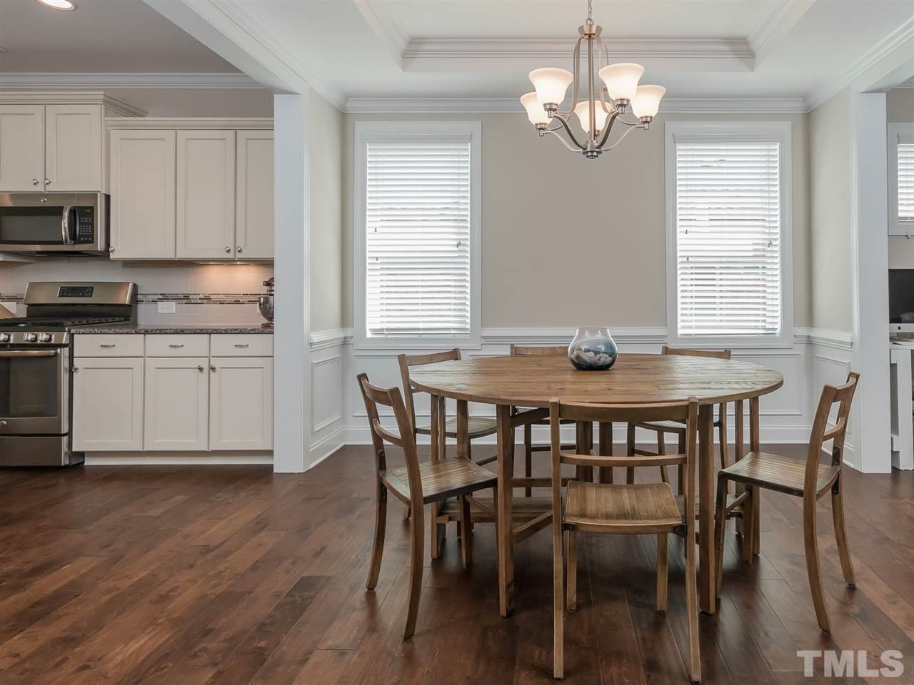 Dining room with trey ceiling and wide plank wood floors.