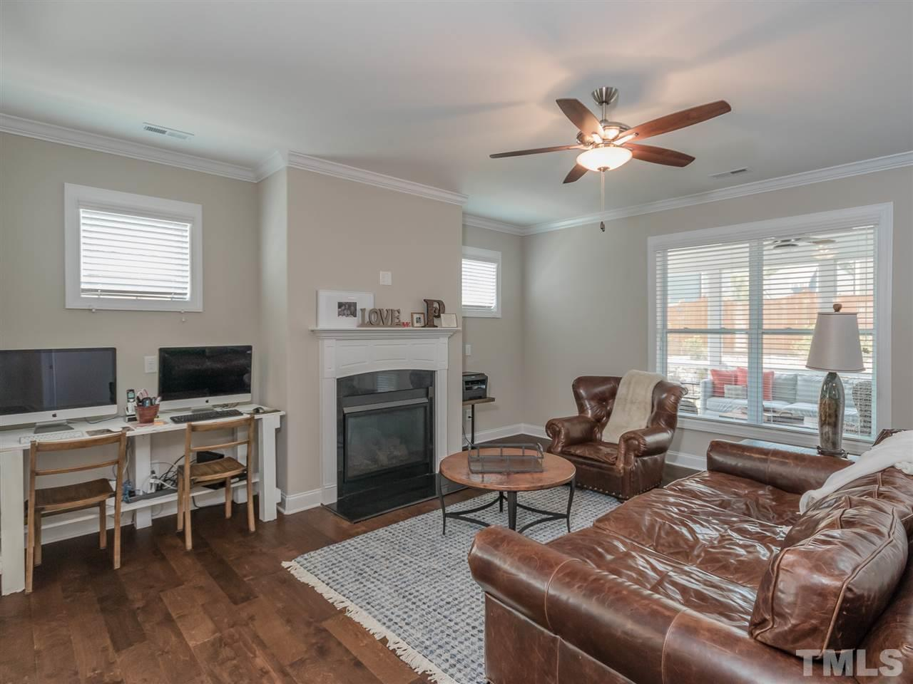 Family room with gas logs and crown molding. Notice the high windows for brings in natural light but does not interfere with furniture placement.