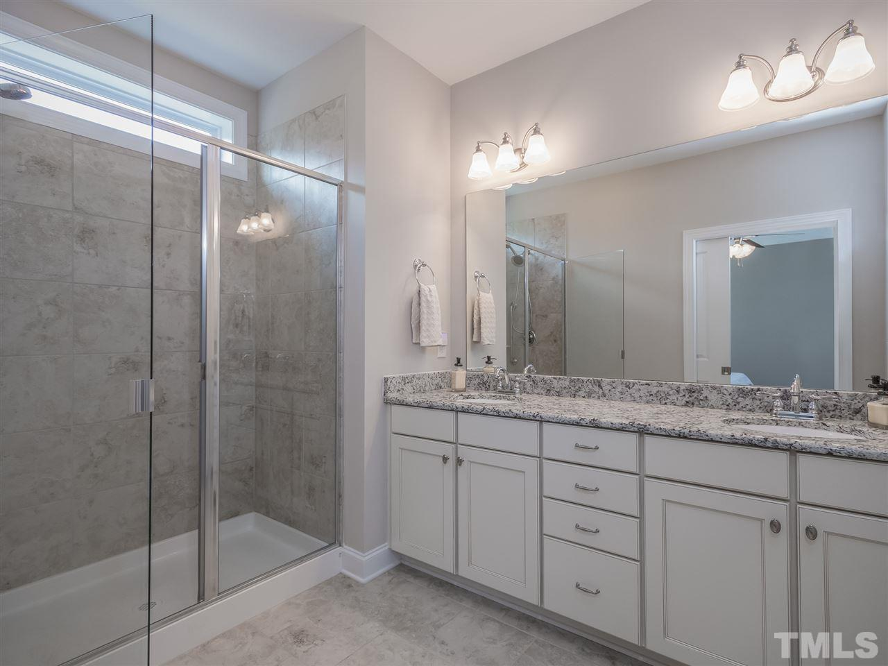 Owner's bath with walk in shower, dual vanities and granite counter tops. The high window brings in great natural light.