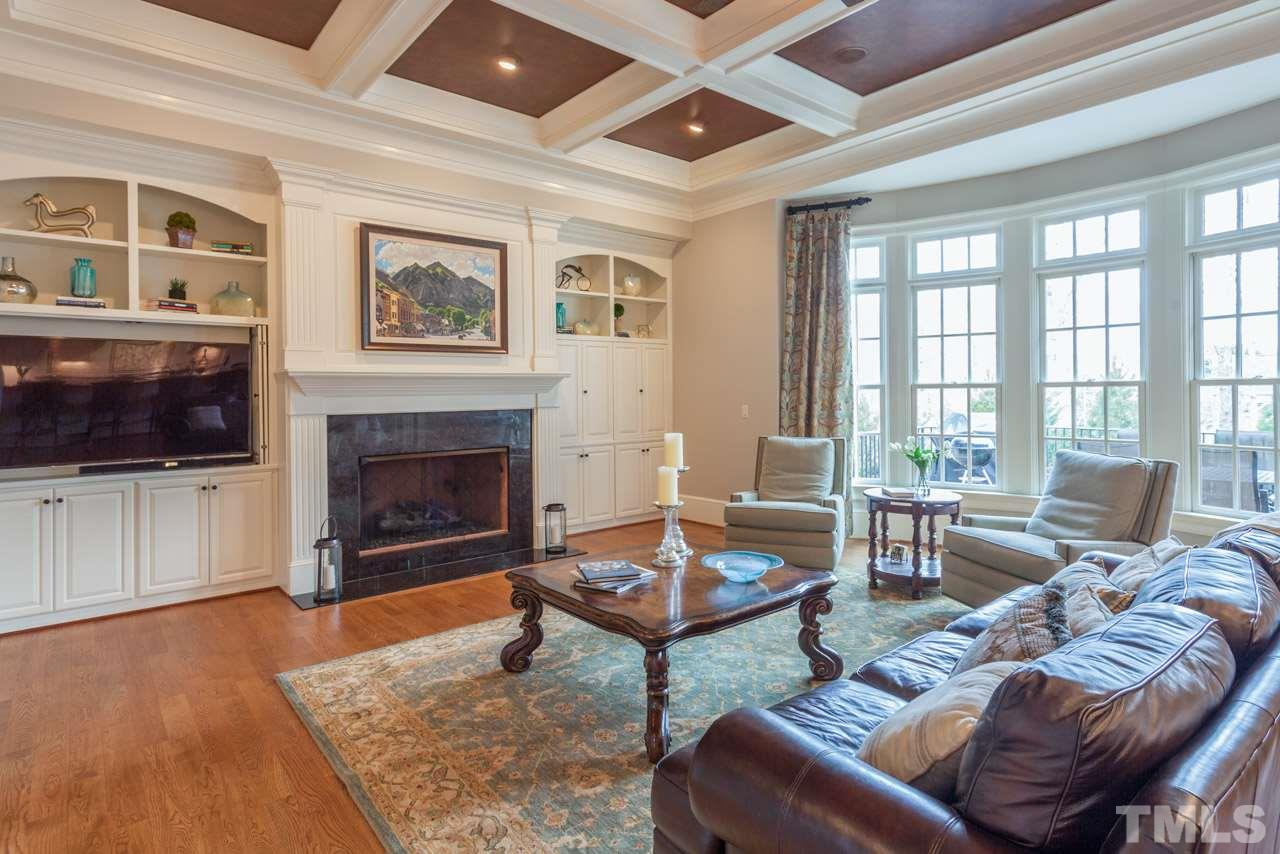 Features include double bookcases that frame the beautiful gas fireplace, dual locations for wide screen television, coffered ceiling with painted faux leather interior, hardwood floors, distributed audio and gorgeous wall of windows overlooking the pool.