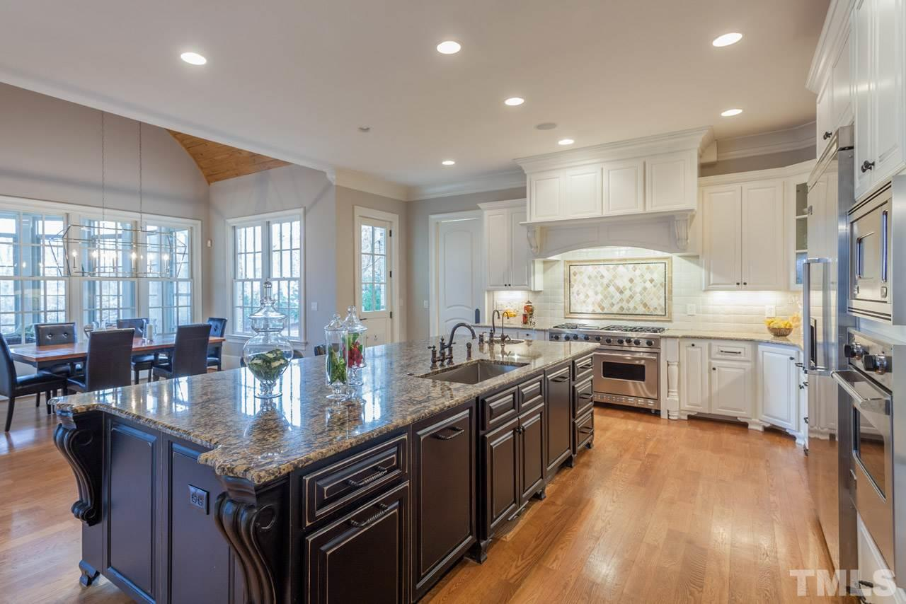 The bright, open kitchen offers an expansive island with 2 separate sinks, granite counter tops, under cabinet lighting, tile backsplash, serving bar w/mahogany counter top, custom cabinets w/pull-out drawers,HUGE walk-in panty, & distributed audio.