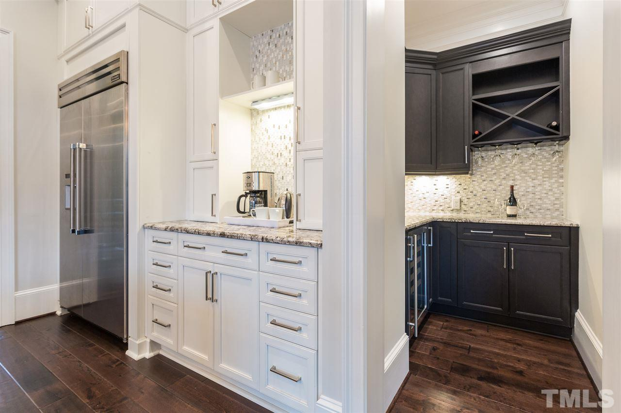 A walk-in butler's pantry is located off the kitchen and provides a wine and beverage mini-fridge, abundant storage, and undercabinet lights. It adjoins an area in the kitchen that provides the perfect location for your coffee and tea makers.