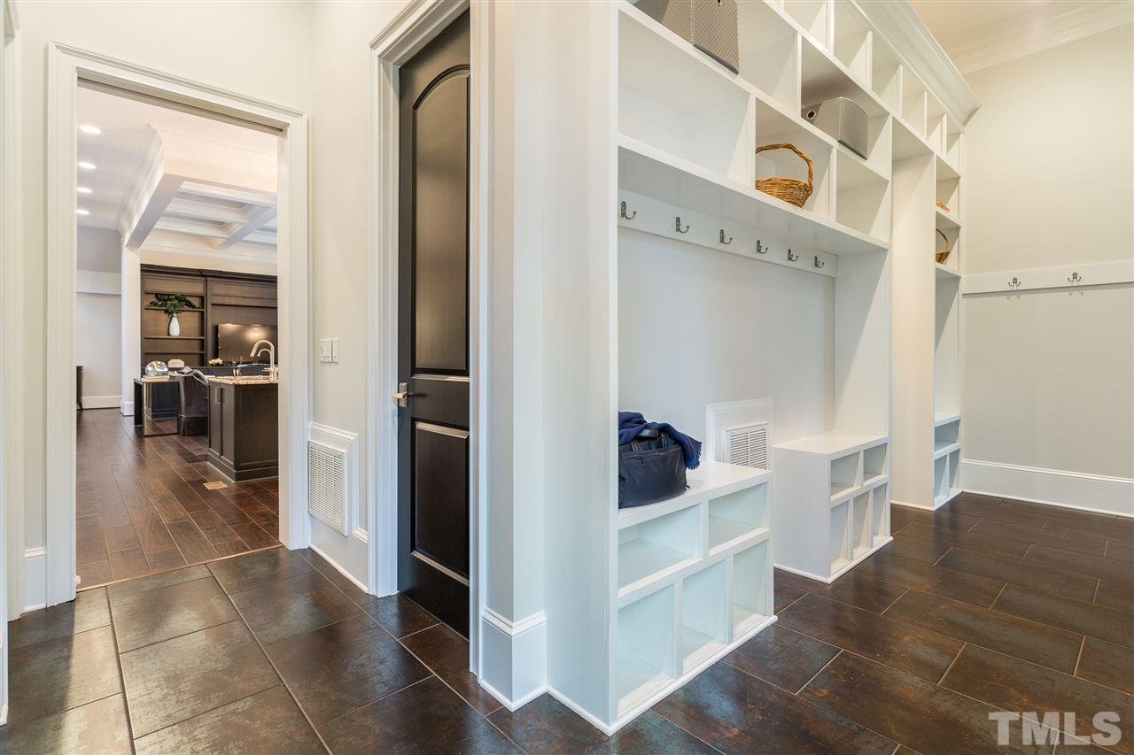 Beyond the kitchen you will find a large mudroom with a wall of custom built-ins as well as a large laundry room, half bath, 2 huge walk in pantries, side entrance to the driveway, and access to the screen porch.