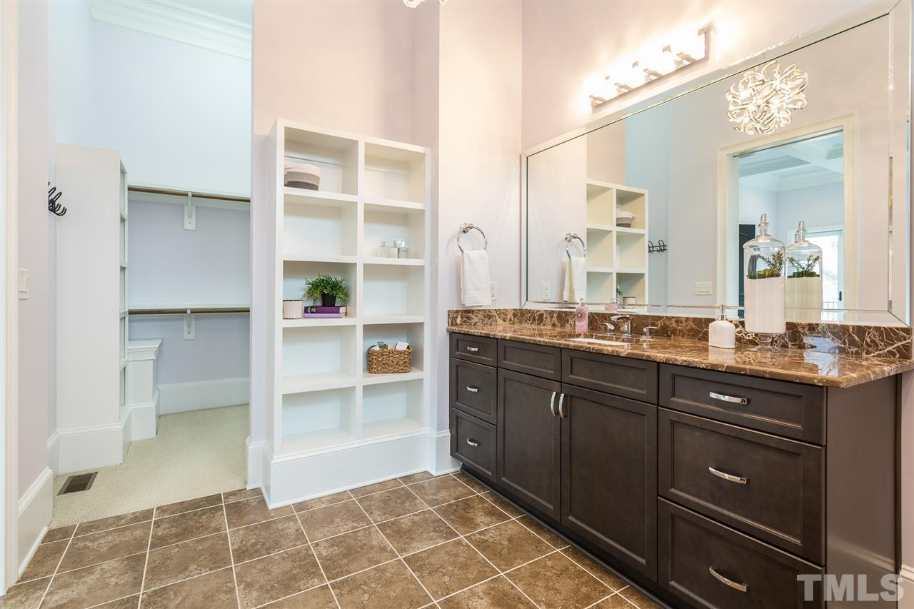 The spacious bathroom features a wall of custom-built open shelving, large vanity would double sinks, a crystal chandelier and a tub/shower combination with tile surround and tile accents.