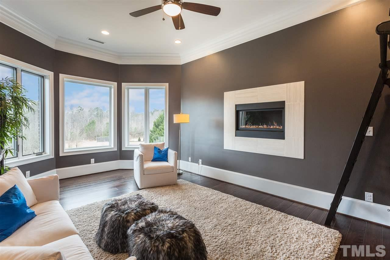 A modern fireplace graces the wall of the library, a beautiful room that overlooks the swimming pool and backyard.  It offers a ceiling fan, crown molding, recessed lighting, hardwood floors and large walk in closet. Bookshelves negotiable( not pictured)